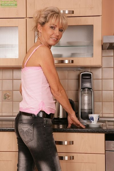 Mature slut with tiny tits Janet Darling poses in her tight jeans