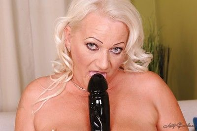 Buxom blonde granny stripping and masturbating her shaved cunt with toys