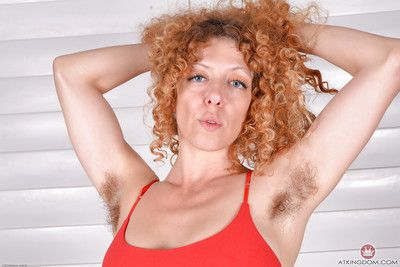 Hirsute older redhead Leona revealing small boobs and erect nipples