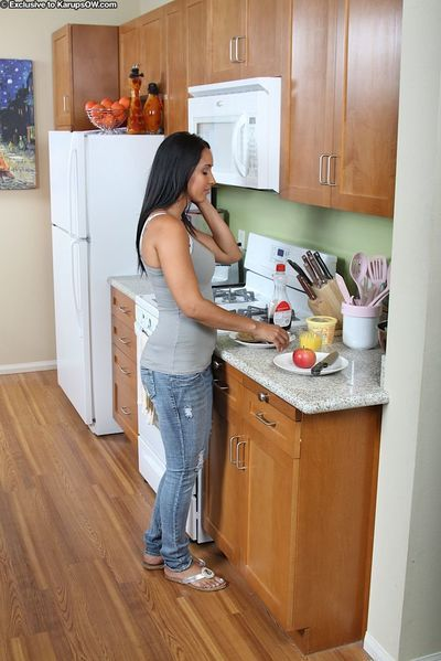 Dark haired latina milf Isis Love with big melons and bald pussy gets nude in the kitchen