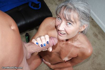 Aged grey haired woman jerks fat cock POV style for cumshot on granny tits