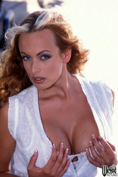 The charming looking milf Stormy Daniels flashing the shaved pussy and big melons outdoor