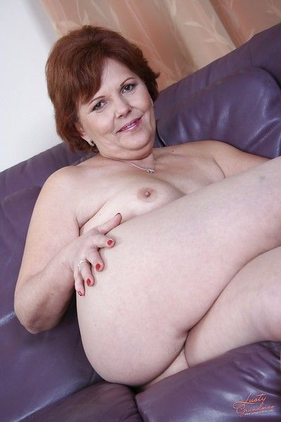 Lustful redhead granny stripping off her clothes and spreading her legs