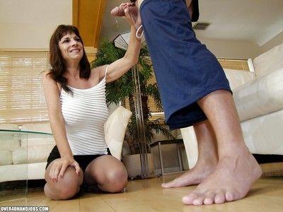 Fuckable mature brunette with massive knockers gives a sensual handjob