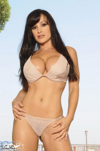 Perfectly shaped brunette Lisa Ann with big boobs strips her lingerie and poses on the chair