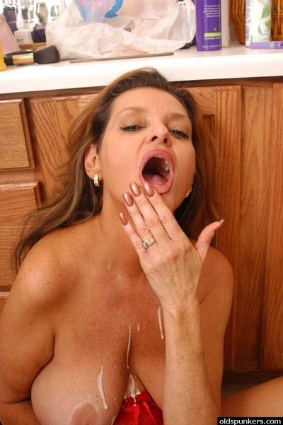 Older lingerie attired broad with big tits giving blowjob in kitchen