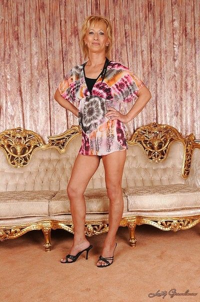Stunning blonde granny on high heels slowly taking off her dress