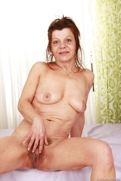 Lascivious granny stripping off her clothes and exposing her hairy twat