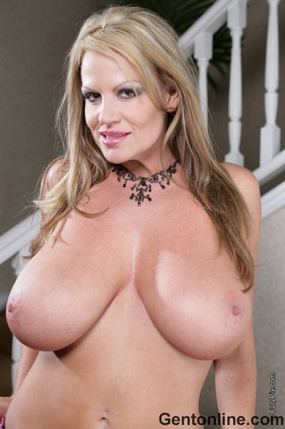 Good looking milf Kelly Madison with massive tits takes off her pink bra and panties