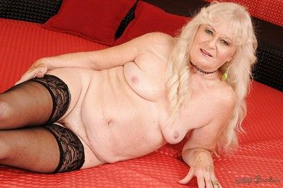 Blonde granny in stockings stripping and posing naked on the bed