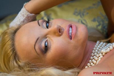 Slim blonde Silvia Saint dressed in white bares her small tits and tight pussy