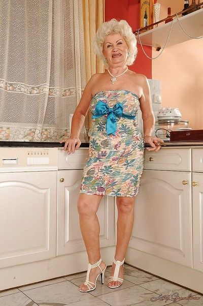 Big busted granny stripping off her dress and panties in the kitchen