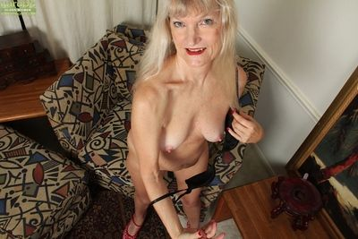 Incredible granny Lisa Cognee teases her shaved pussy and ass while undressing