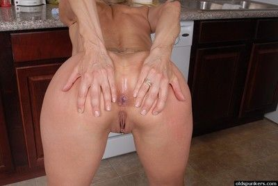Busty blonde granny Charlotte licking her own nipples in the kitchen