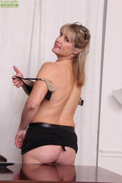 Mature woman Rebecca Hill freeing bare ass from leather skirt in heels