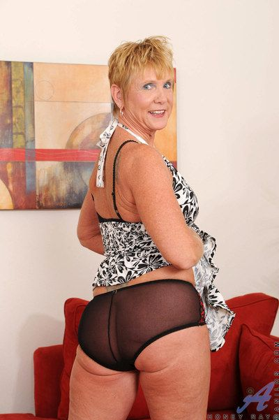 Short haired blonde granny Honey Ray freeing big tits and ass from lingerie