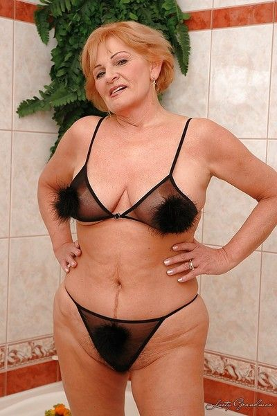 Horny granny with huge boobs plays with her cunt in the shower