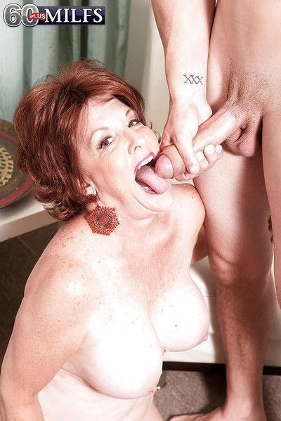 Redheaded granny Gabriella LaMay unleashing big tits before giving blowjob