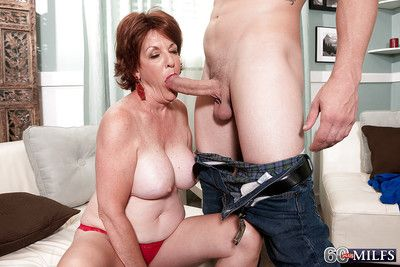 Redheaded granny Gabriella LaMay unleashing big tits before giving blowjob