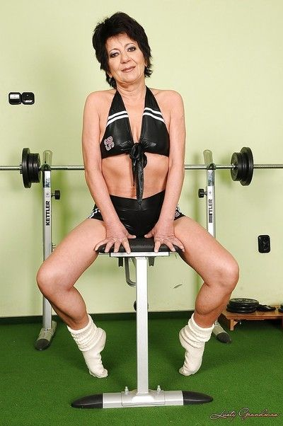 Sporty brunette granny with tiny tits stripping in the gym