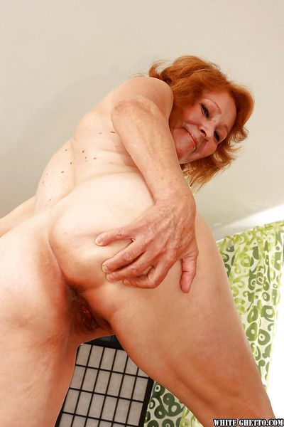 Filthy redhead granny with shaved cunt stripping and spreading her legs