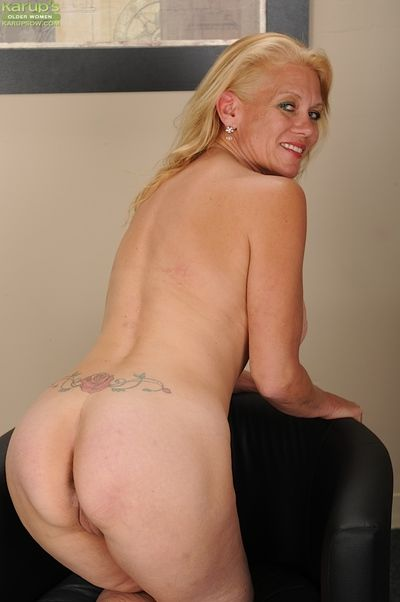 Mature blonde with huge round boobs getting nude and demonstrating her gash