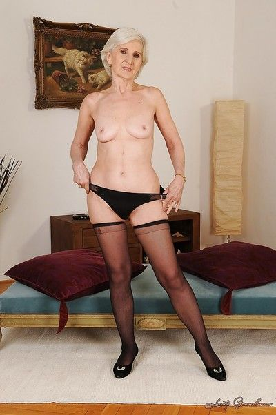 Slim granny in stockings slipping off her dress and lingerie