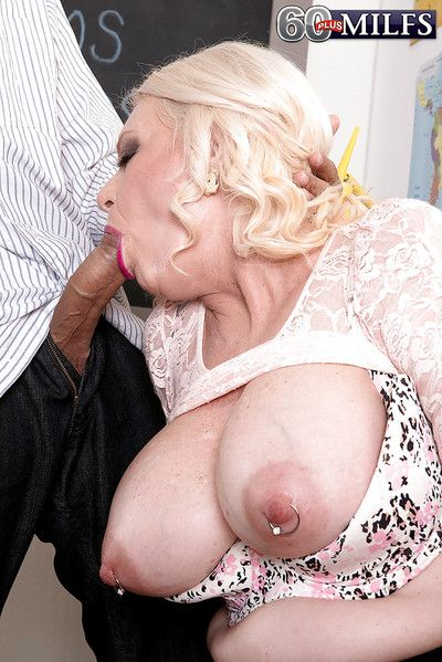 Blonde granny Angelique DuBois exhibiting pierced nipples while giving BJ