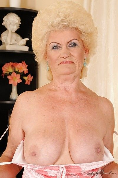 Full-bosomed blonde granny stripping and showcasing her shaggy twat