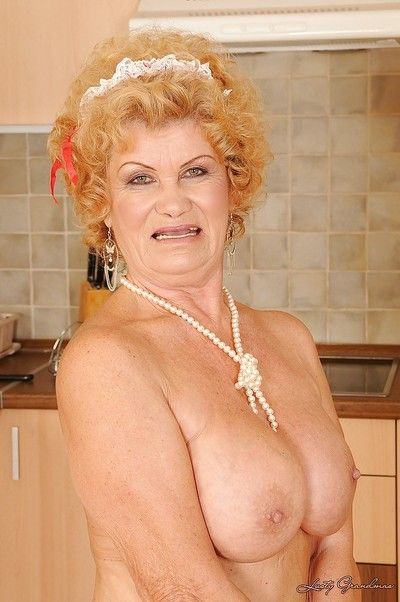 Lusty granny in maid uniform and stockings stripping in the kitchen