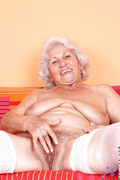 Blond granny in shiny white stockings denudes boobs and masturbates