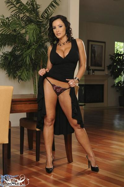 Lecherous brunette Lisa Ann strips her black evening gown and shows her big boobs