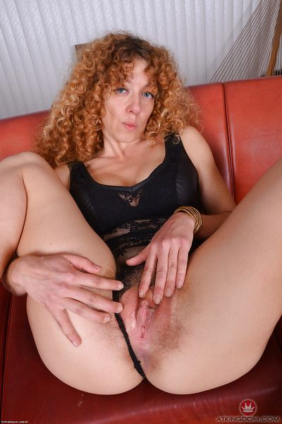Older hirsute redhead Leona baring big boobs in leather shorts and heels