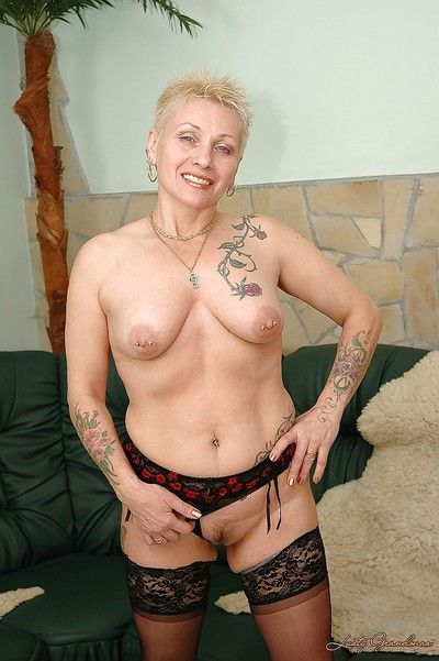 Short haired tattooed granny with pierced nipples taking off her lingerie