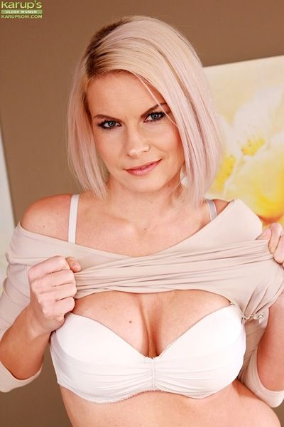 Mature blonde Endy Clinton revealing round boobs in white mesh stockings