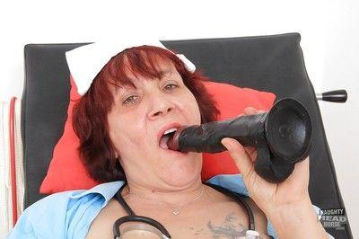 Redhead granny Manka takes off her sexy nurse uniform on cam
