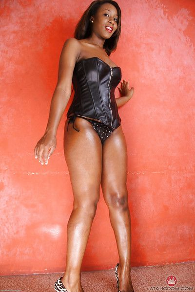 Older ebony model Chiya showing off great legs in leather bustier