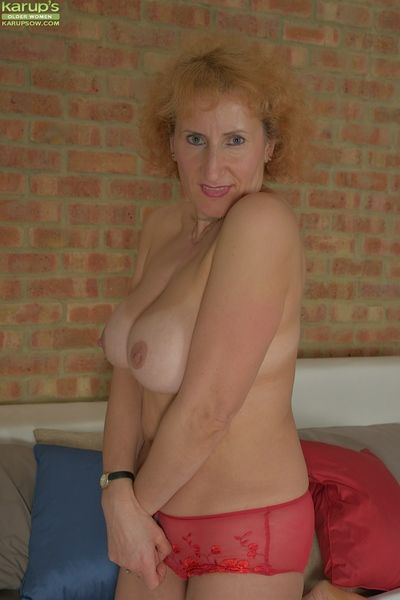Aged redhead Naomi Triplexxx showing off nice pair of granny boobs