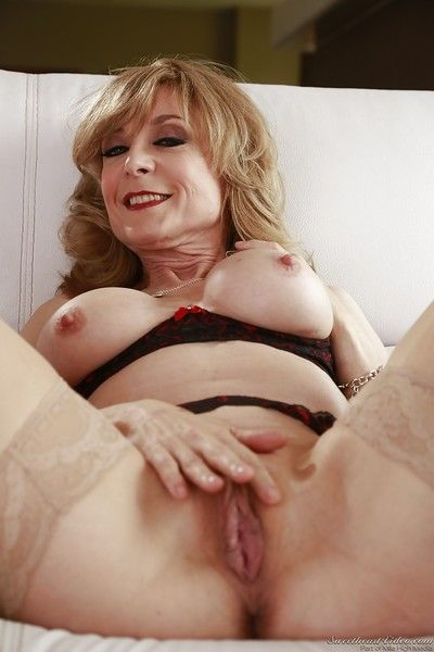 Mature hottie in stockings plays with her big tits and spreads her cunt
