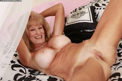 Older woman Cam Rayea revealing large fake tits and pussy on bed
