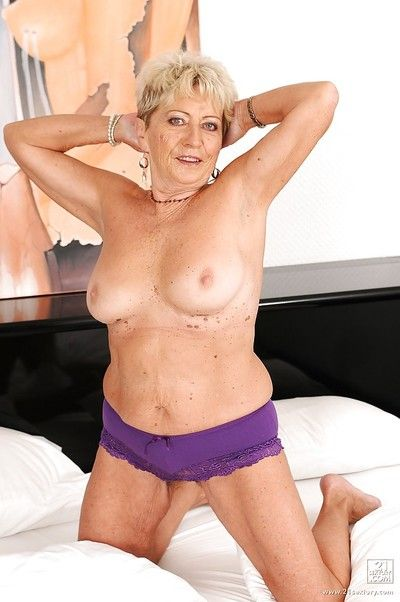 Chubby granny with shaggy twat taking off her lingerie on the bed