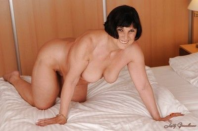 Smiley brunette granny uncovering her fatty curves on the bed