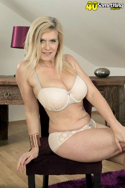 Blonde mature mom Marina Rene undressing to flaunt pierced big tits