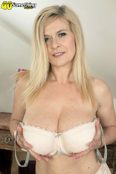 Blonde mature mom Marina Rene undressing to flaunt pierced big tits