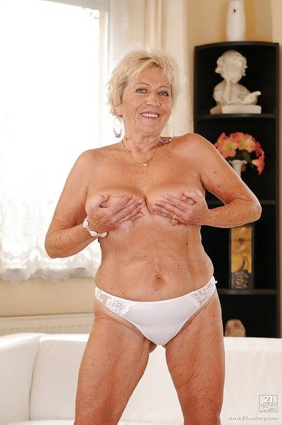 Playful granny with massive jugs stripping and showcasing her shaggy cunt
