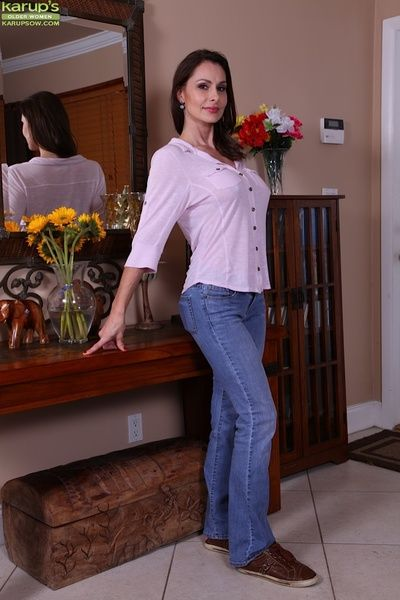Mature brunette Nora Noir slips out of her blue jeans.