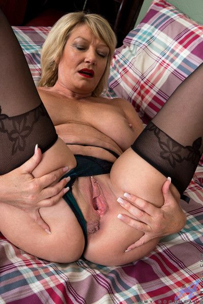 Excited mature in fingering action in the bedroom