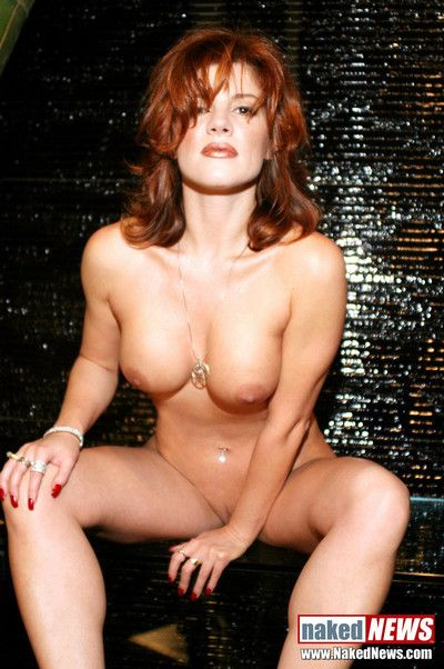 An arousing redheaded model strips down to show her immaculate sculpted breasts