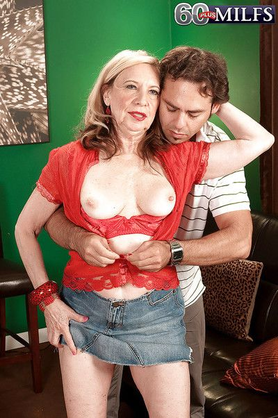 Miranda Torri showing her granny tits in red underwear while stroking a cock