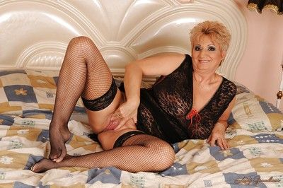 Filthy granny in stockings stripping on the bed and licking her nipples